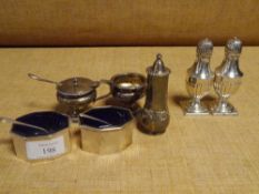 A group of silver condiments comprising: an Edwardian three piece set of salt, pepperette and