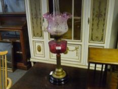 A Victorian cranberry glass and brass oil lamp, with ebonised base, columnar standard, cranberry