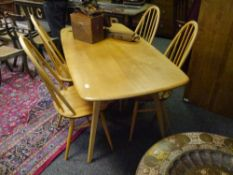 An Ercol light elm dining table and four chairs, the table with rounded corners and raised on square