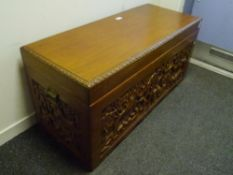 A South-East Asian camphorwood chest, carved with figural panels and fitted with carrying handles.