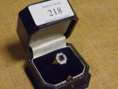 A sapphire and diamond flowerhead cluster ring, the emerald-cut sapphire within a band of eight