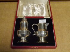 A cased silver sugar caster and cream jug, Birmingham 1936 and 1937, of hipped baluster form. 6 troy