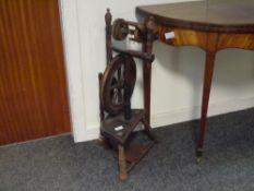 A small oak spinning wheel, c. 1900, raised on splayed turned legs. 0.79m