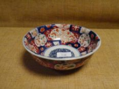 A Japanese Imari porcelain bowl, decorated in the characteristic palette with floral reserves. 18.