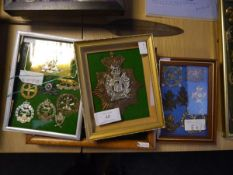 A group of British military cap, shoulder cross belt badges and buckle, mounted in five frames,