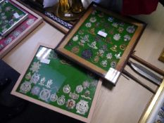 A collection of military cap, shoulder and cross-belt badges, mounted in two frames, including