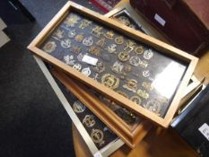 A collection of British military cap, shoulder and cross-belt badges, mounted in three frames,