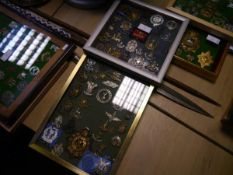 A collection of British military cap, shoulder and cross-belt badges, mounted in two frames,