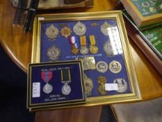 A framed group of military cap badges, buckle etc including Argyll & Sutherland Highlanders, Cameron