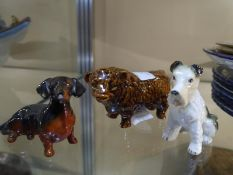 Three small pottery animal models, a fox terrier stamped Beswick, a highland cow and a dachshund (