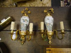 Pair of gilt-metal mounted porcelain twin-light wall sconces, each with floral spray surmount over a