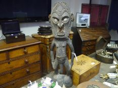 Large carved wooden tribal figure, probably Papua New Guinea, the grimacing face with inset shell