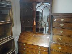 George III mahogany bureau bookcase, c. 1800, the moulded cornice above a plain frieze over a pair