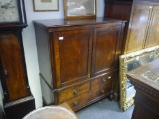 19th century mahogany low linen press, the panelled doors enclosing slides, above two short and