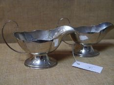 Pair of George V silver sauceboats, Birmingham 1925, of faceted form, on oval domed feet. 10.47 troy