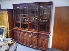 George III style mahogany breakfront bookcase, with fretwork carved frieze above astragal glazed
