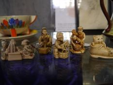 Collection of Japanese ivory netsuke including Beijin kneeling with hand mirror, cat within boot and