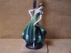 1930s figural porcelain table lamp, of Goldscheider type, the girl modelled in dancing pose in green