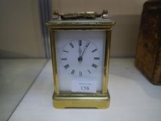 Early 20th century gilt-brass carriage clock, the white enamel dial with Roman numerals, with key.