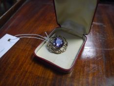 9ct gold amethyst brooch, the circular-cut stone within an open scroll mount.