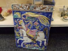 A large tile in the Indo Persian taste moulded with a mounted huntsman and polychrome glazed