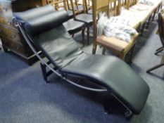 A Le Corbusier style chaise upholstered in black leather on a chrome frame