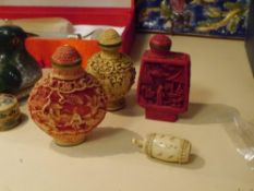 Two Chinese faux ivory snuff bottles together with a cinnabar lacquer Chinese snuff bottle