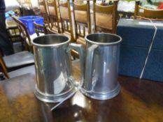 "A pair of pewter novelty golfing tankards, each glass bottomed, one inscribed ""the 19th hole"" the"