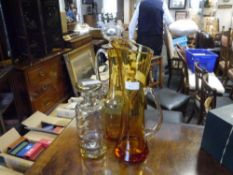 An amber glass decanter and jug, possibly Holmegaard, together with a ribbed glass decanter in the