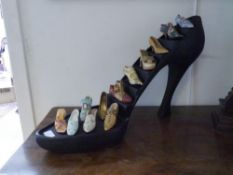 "A group of resin ""Just The Right Shoe"" models including Versailles and Golden Stiletto, on a display"