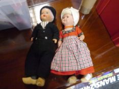 A pair of vintage Dutch boy and girl dolls, she with glass eyes, he painted, both in wooden clogs