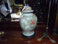 A Chinese porcelain baluster jar and cover in the famille rose palette decorated with figures