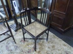 An Edwardian cane-seated corner chair with shell carved crest rail