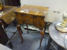 An early 20th century walnut side table in the form of a lowboy, with three drawers and raised on