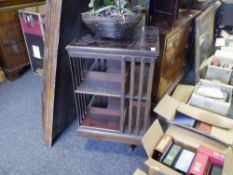 An early 20th century mahogany revolving bookcase, the three tiers joined by splat urprights
