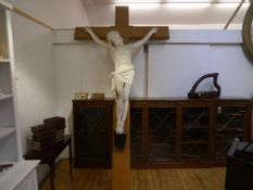 A late 19th century lifesize plaster figure of the Crucified Christ, mounted on a grain-painted