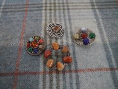 A group of four Scottish white metal pebble and hardstone brooches, including Miracle, largest 4.2cm