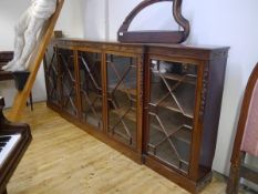 A George III style mahogany low breakfront bookcase, the moulded top above a fretwork carved