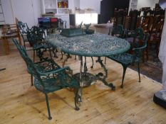 A green painted cast metal garden dining table and a pair of two seater garden benches, in period
