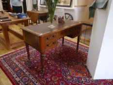 A mid-Victorian walnut writing table, the faux-leather inset top with rounded corners above a frieze