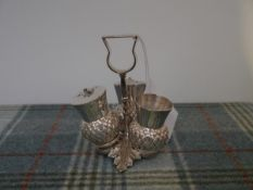 An electro-plated Britannia metal three piece thistle condiment set, salt, pepper and mustard, on