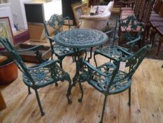 A green painted cast metal garden table with four open armchairs, in period style