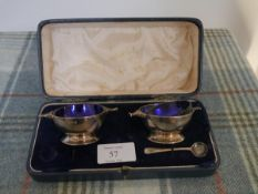 A pair of George V silver quaich-form salts, London 1927, each with blue glass liner, one spoon,