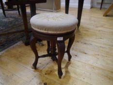 A late 19th century mahogany piano stool, the adjustable circular needlework seat raised on four