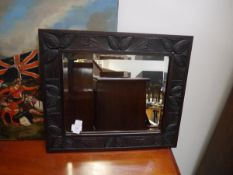 An Arts & Crafts oak mirror, probably Scottish, the rectangular bevelled plate within a conforming