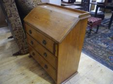 A golden oak bureau in the Arts and Crafts taste, c. 1900, with galleried top above a slope