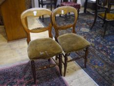 A pair of Victorian balloon back side chairs, of characteristic form, on turned legs and stretchers