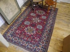 A Bijar rug, with geometric and foliate pattern on a red ground. 170cm by 107cm
