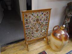 A needlework firescreen, in a light oak frame. 76cm by 51cm
