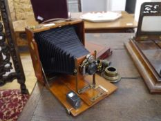 """An early 20th century folding plate camera, with mahogany case, the shutter signed Bausch & Lomb """""""